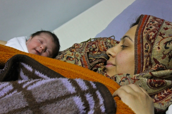 Hanadi, 23, from Homs, Syria lays in Akilah Hospital in Amman, Jordan with her newborn daughter, Rasmeen. Akilah Hospital provides free healthcare to refugees who've fled the war for the safety of Jordan.