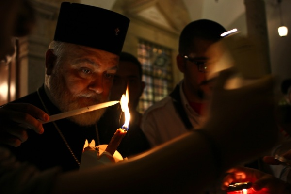"The priest transfers the ""Holy fire"" to church patrons."