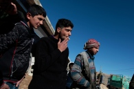A group of young men listen and discus the situation between the opposition and Jabat al Nusra fighters. The men here fled Syria less than three months ago. They are working in a motor bike repair shop in Arsal. Photo by Omar Alkalouti.
