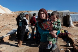 Woman and her child receive an medical examination and gifts for the holidays from volunteers from Lebanese for Syrians. Photo by Omar Alkalouti.