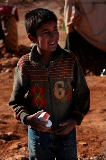 A young Syrian boy smiles as he receives medicine from the Lebanese for Syrians group after being examined by the volunteer doctor, Dr. Nick Batley. Photo by Omar Alkalouti.