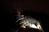 Syrian woman suffering from frostbite and other ailments as she is being examined by volunteer Doctor Batley in her home with no electricity or running water. Photo by Omar Alkalouti.
