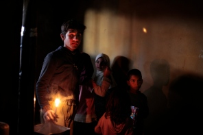 Ahmad, 13, and his siblings come to watch their mother be examined by volunteer Dr. Batley. He brings a candle to show the doctor the frostbite on his mothers feet that is badly infected. There house has no running water, electricity, or furniture. The woman rest on a small mat on the floor of a dark shelter that the family of ten occupied when they fled the fighting in Al Qusair, Syria. Photo by Omar Alkalouti.