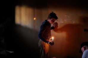 Ahmad lights the room with a candle for Dr. Batley to examine his mothers frostbite feet, Ahmad lives in an area outside of Arsal past the last Lebanese military check point and the borders of Syria. He is from Al Qusair and fled with his family when heavy clashes broke out between Syrian regime forces and opposition group. Photo by Omar Alkalouti.
