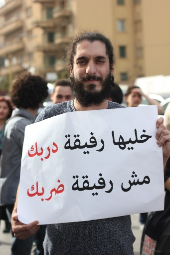 "Nizar Najjar, 28, holds a sign that reads, ""Make her a partner in your path, not a partner for your beating."""