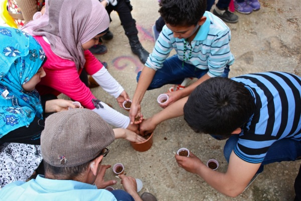 Syrian refugees from a nearby village learn how to plant basil seeds as part of Italian NGO Intersos' psycho-social services that focus on diverse ways to educate children.