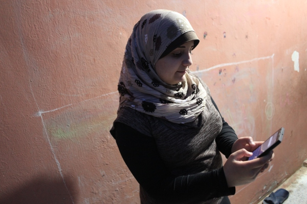 "Amal Haddad holds her mother's cell phone in her hand, with the app, ""Smart Dictionary,"" that she uses to help her with her homework."