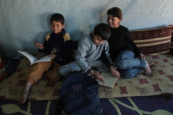 Faisal, 6, Hazim, 7, and Asmahan, 11, flip through Hazim's books in their tented home in the Masaab Telyani camp Zahle, Lebanon.