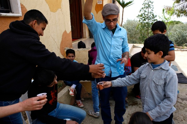 Firas Abi Ghanem, Intersos project coordinator in the Chouf, runs an activity where he is helping a new group of Syrian refugees learn how to let the water out of the bottom of their cups, which have freshly planted basil seeds.