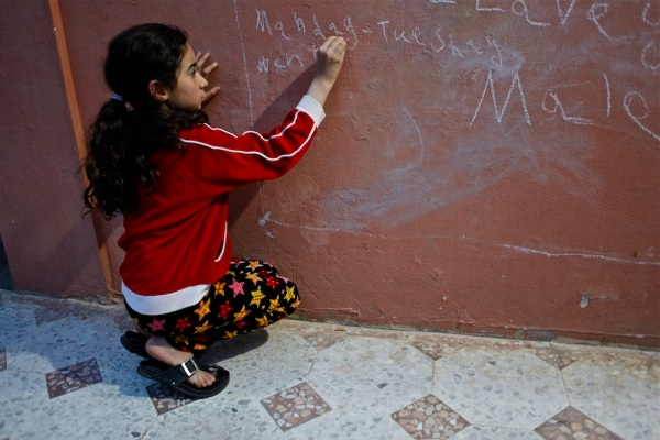 "Ahlam Haddad, 9, in the village of Ktermaya, Lebanon, wants to be an English teacher and practices her English daily on her ""chalkboard"" on the outside wall of her family home."
