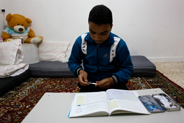 Alaa Haddad has his mathematics book out where he does his homework every night. Mathematics is his favorite subject.